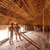 Foto disponível na campanha.Índios Yawalapiti com tunacape (cocar) tocando a flauta Uruá no interior da maloca (oca) reservada aos homens (Casa dos Homens), na aldeia Yawalapiti por ocasião do Kuarup em homenagem ao antropólogo Darcy Ribeiro,2012 (Rogério Reis)